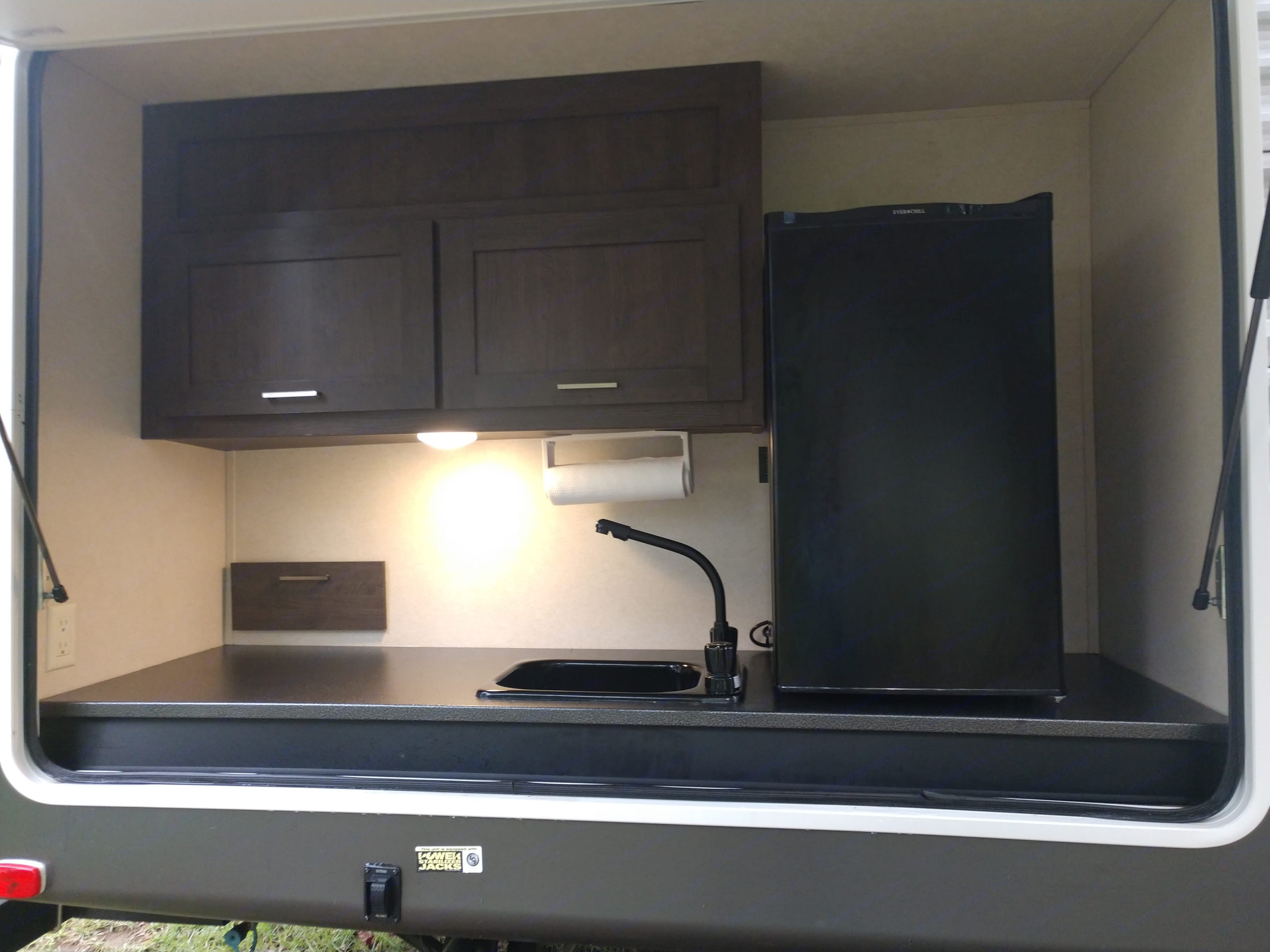 Outdoor kitchen area with sink and mini fridge . Forest River Salem 2018