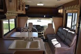 Interior  Facing Forward, Shows the seating capacity for multiple travelers. The couch folds out into a double bed and the table will convert to a double as well, or place them both down and use as a Larger Queen Bed. The space above the cab is also a double sleeping space with a TV that swivels out for full viewing.. Coachmen Freelander 2016