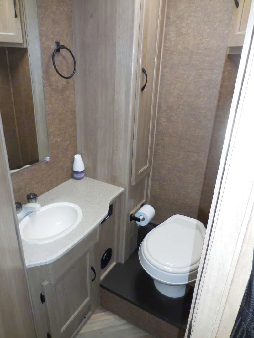 Bathroom contains a small sink and toilet, plenty of cabinets for towels and toiletry items. . Coachmen Freelander 2016