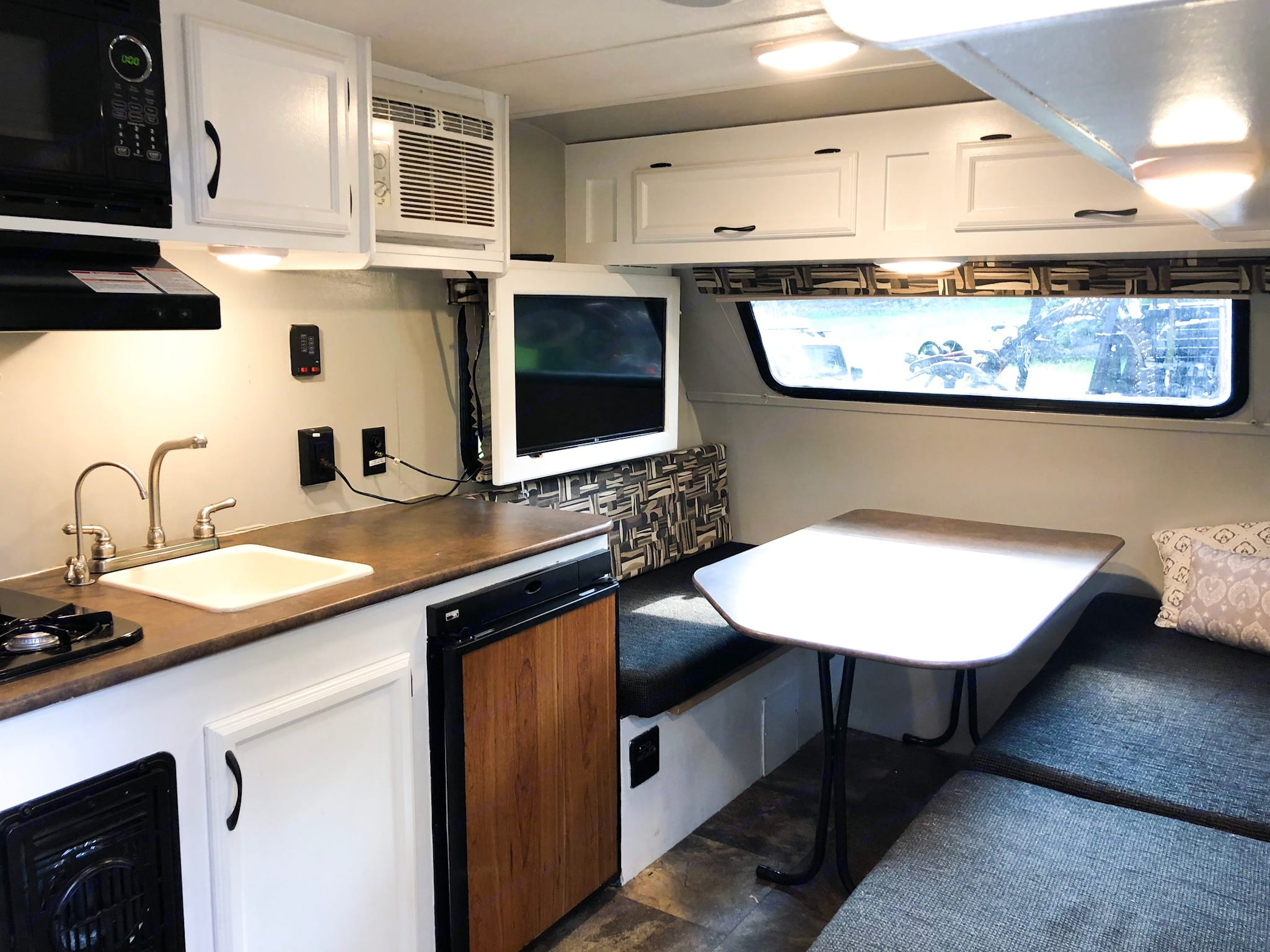 The interior of the camper. On the left you see the kitchen. On the right is a full length bench that continues into the dining table. The table folds down to sit in between the two far benches. The cushions can then be laid on top to make a comfortable bed. Or, if you would prefer a little more comfort, it's a great place to lay your air mattress on top!. Starcraft Ar-One 2016
