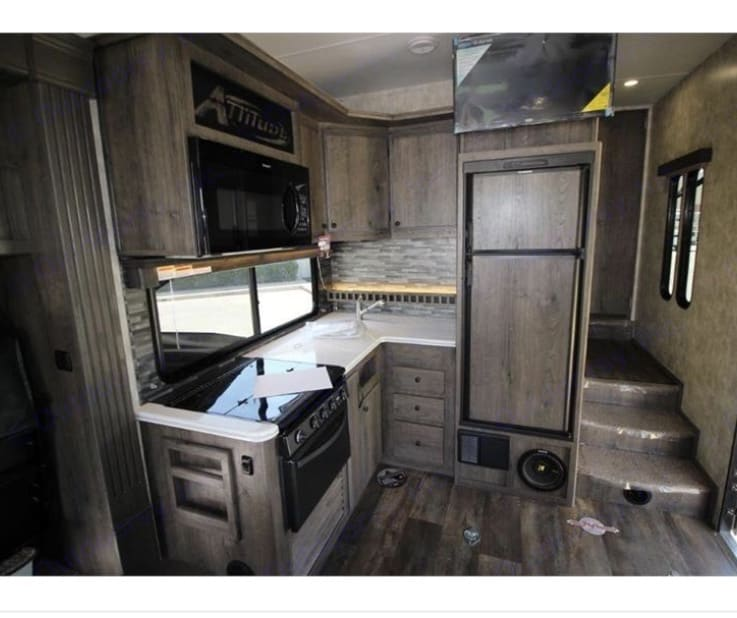 Kitchen area with microwave, stove and fridge. Tv and surround sound system . Eclipse Recreational Vehicles Attitude 2018