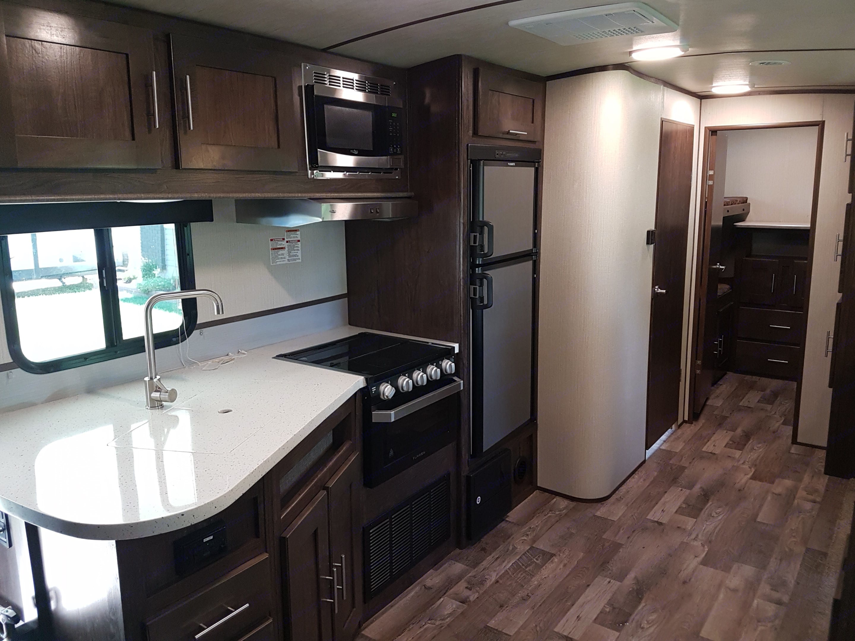 Spacious Kitchen with Bathroom door on left & private bunk room at back. Cruiser Rv Corp Radiance 2019