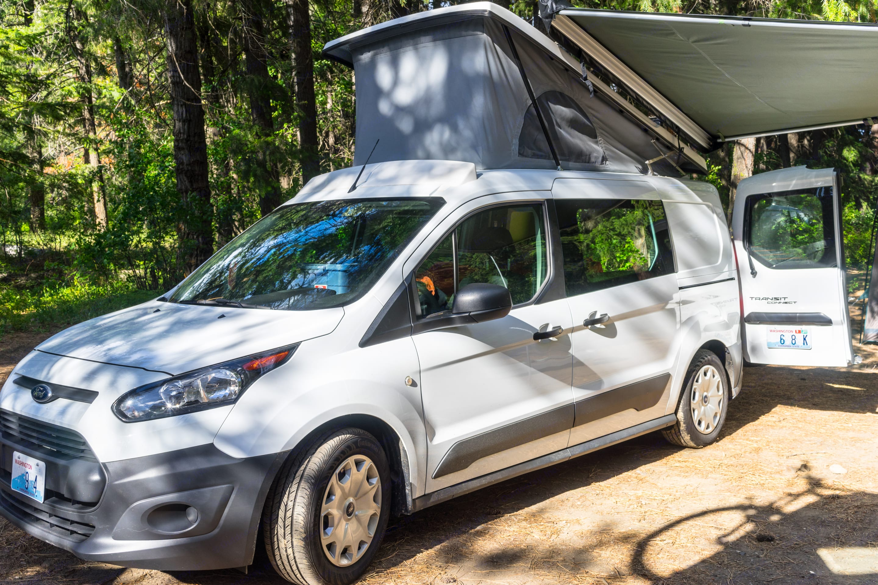 """The pop-top creates 6'4"""" of standing room inside. Outside, the awning can be used with the top up or down.. Ford Transit Connect 2016"""