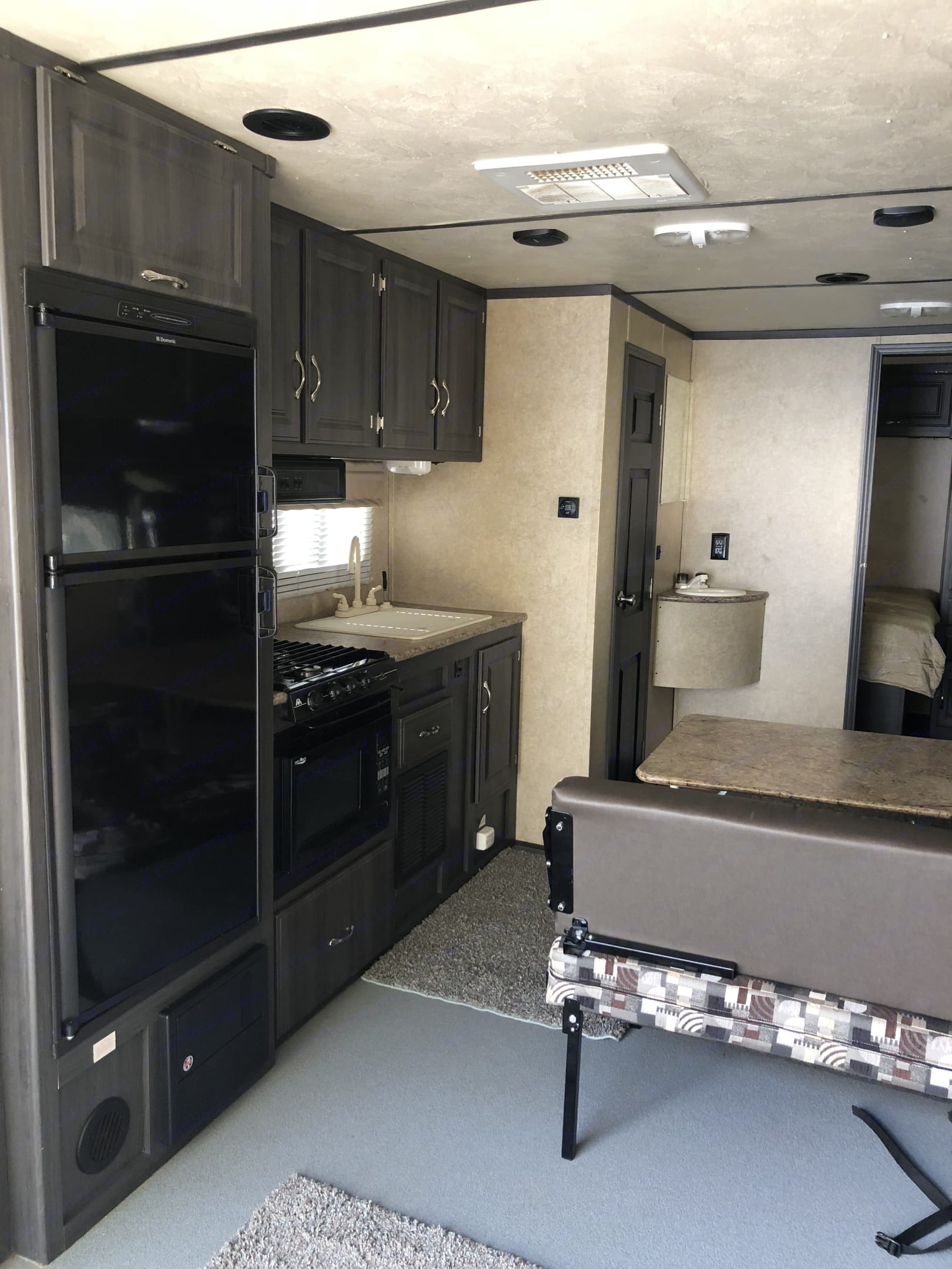 Kitchen/dining area all ready for those family meals together!  Includes a convection/microwave oven combo, 3 burner stove top. . Forest River Work And Play 25UDT 2013