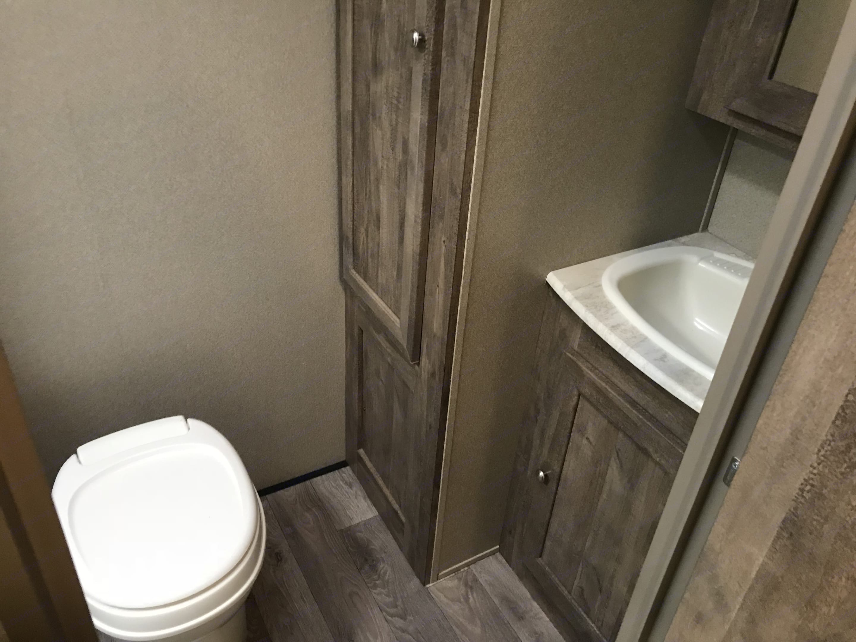 private washroom with a sink, toilet and stand up shower. Forest River Puma 2018