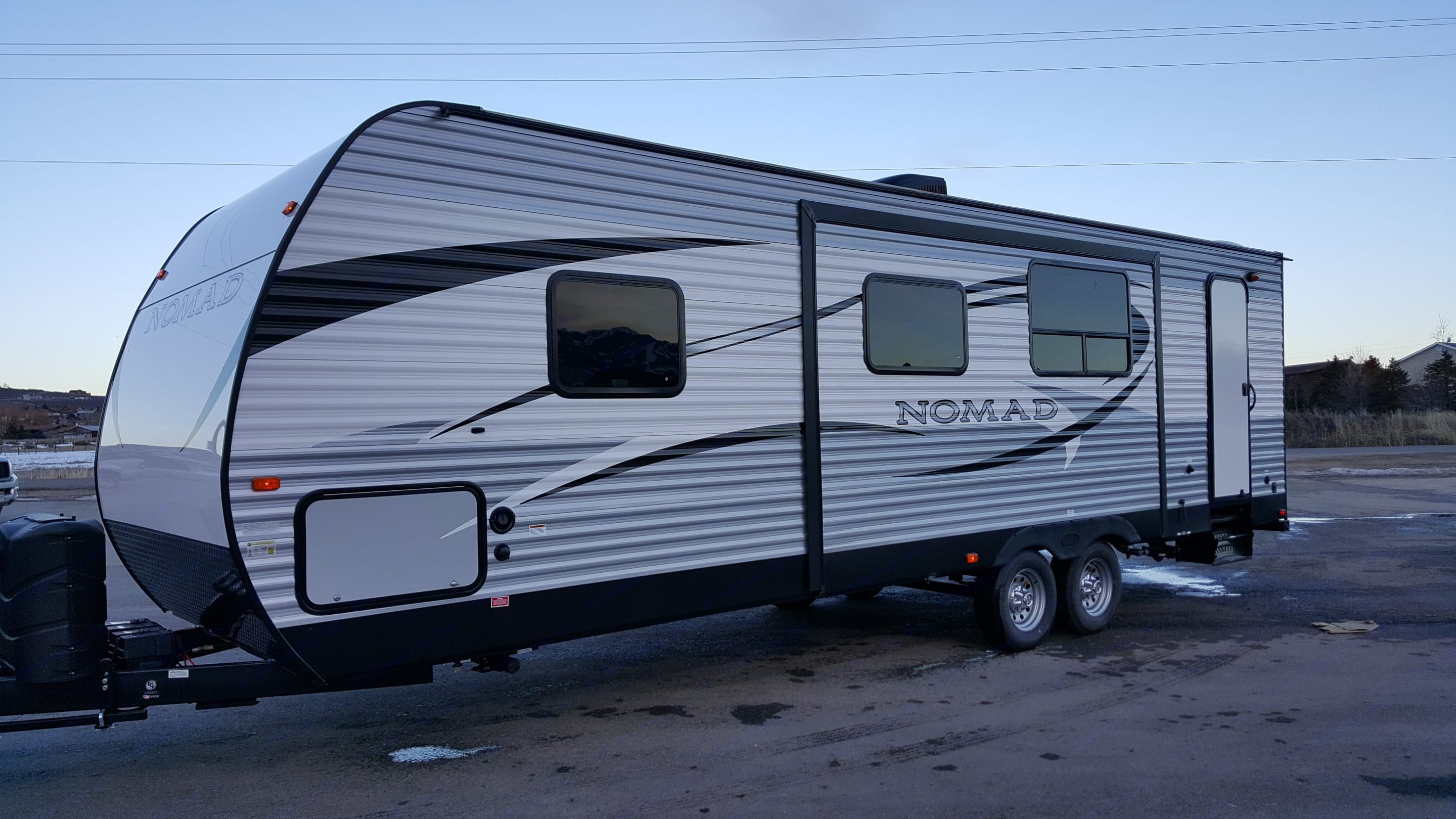 Main door is on the other side of this trailer, but this shows the slide and the exterior bathroom door. This trailer also features a automatic retractable awning with led lighting and speakers. Also a outdoor kitchen with mini fridge, sink and cabinets. . Skyline Nomad 2016