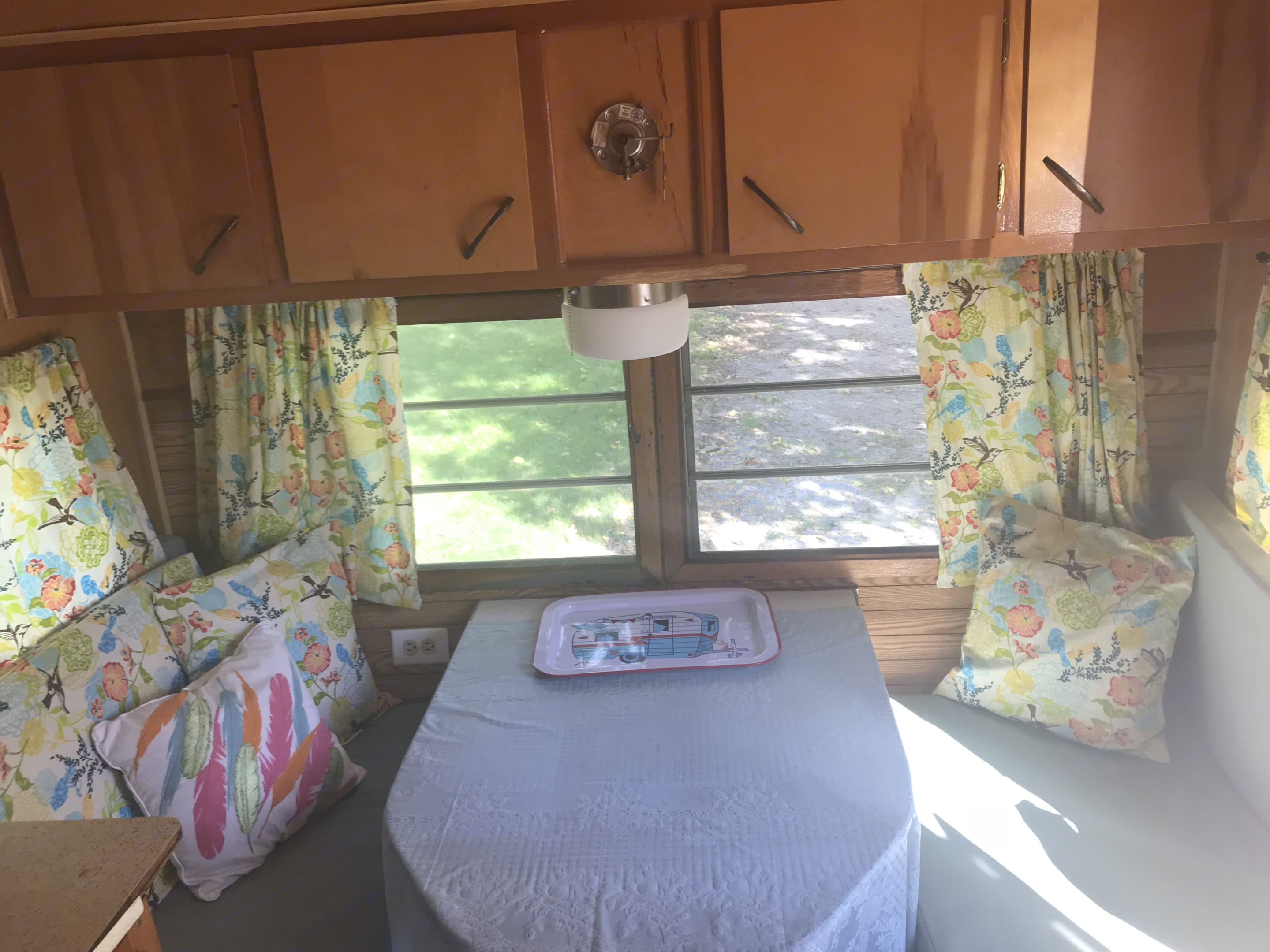 Comfy dinette provides a great place for lunch or to play cards if it rains during your trip!  It also folds down and coverts to a twin size bed if you need the extra space!. West Wind Frolic 1965