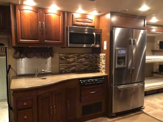 kitchen with residential refrigerator. Coachmen Encounter 2013
