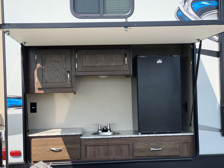 Outdoor kitchen includes fridge, sink, lots of storage, outdoor coffee maker, cooktop stove.. Dutchmen Aerolite 2017