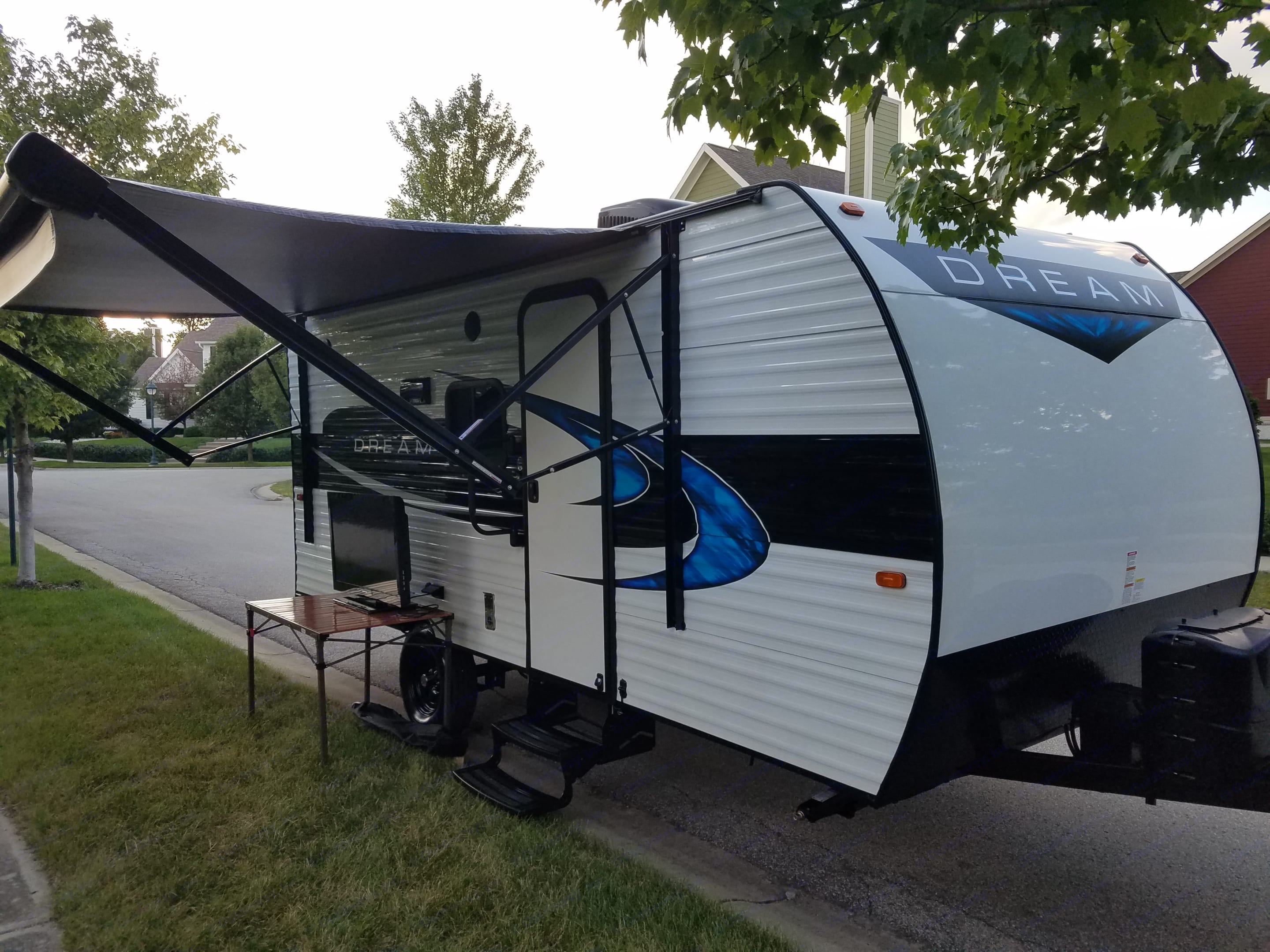 Front side of camper with awning out & outdoor tv set up.  Table is provided with rental. Riverside Rv Other 2019