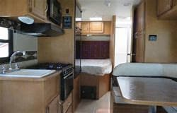 Kitchen has microwave and hooded fan over stove...1 sided sink and storage underneath.. Winnebago Minnie Winnie 2015