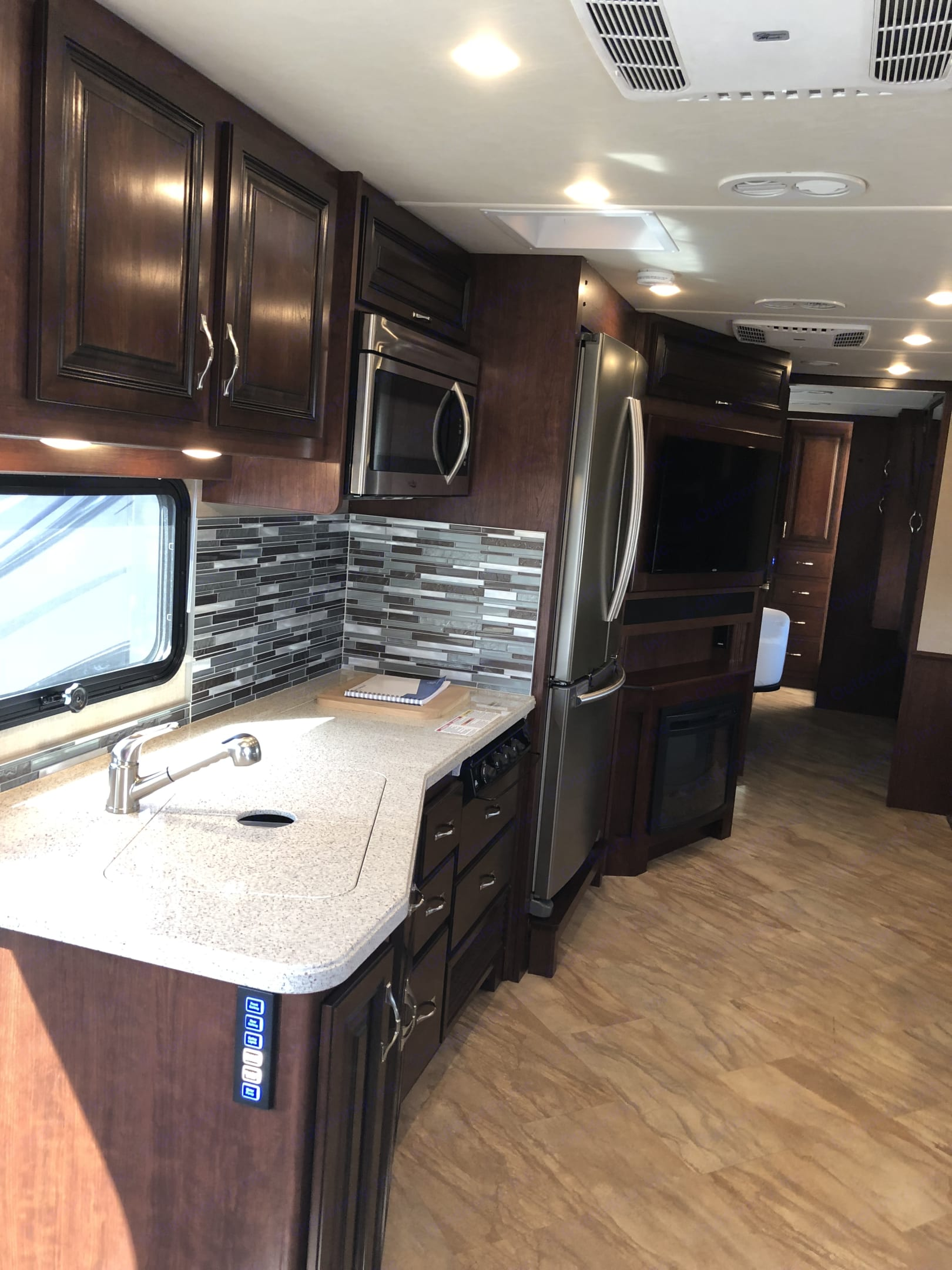 """Kitchen with the full size residential french door refrigerator, 3 burner cook-top, microwave and convection oven combo.  The living area features a 40"""" flat screen TV above a functional electric fireplace to keep you warm in the winter months. . Holiday Rambler Vacationer 35K 2017"""