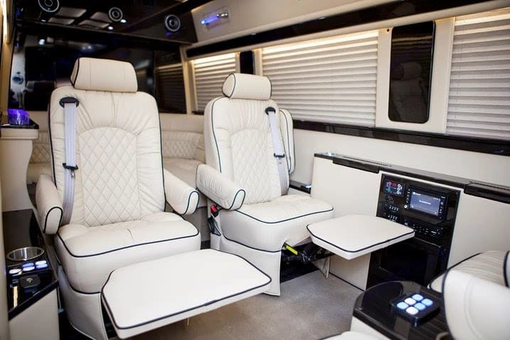 Plush reclining captain's chairs with power leg lifts and wood lap tables. Ultimate Toys Ultimate Limo 2019
