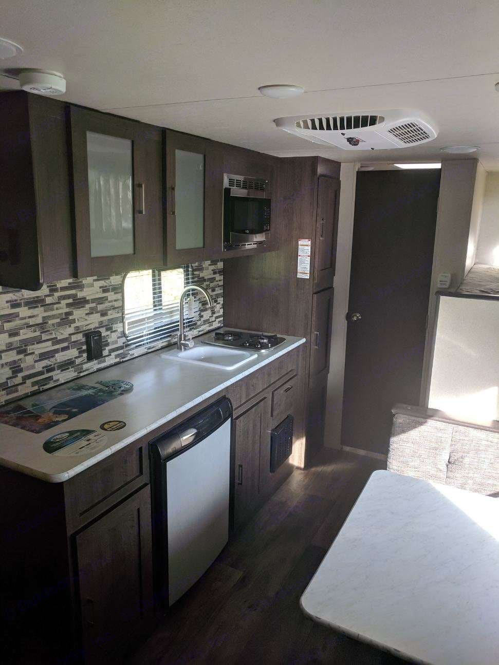 Small fridge, 2 burner oven, microwave and cabinet space. Forest River Wildwood 2018