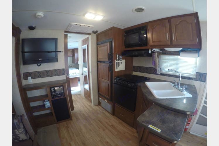 Looking from living area towards the front of the trailer. Kitchen to the right. Tv, Stereo, and Pantry storage to the left, Entrance through pocket door down the center to gets you to the Bathroom, Shower Room, and Master Bedroom.. Fleetwood Wilderness 2009