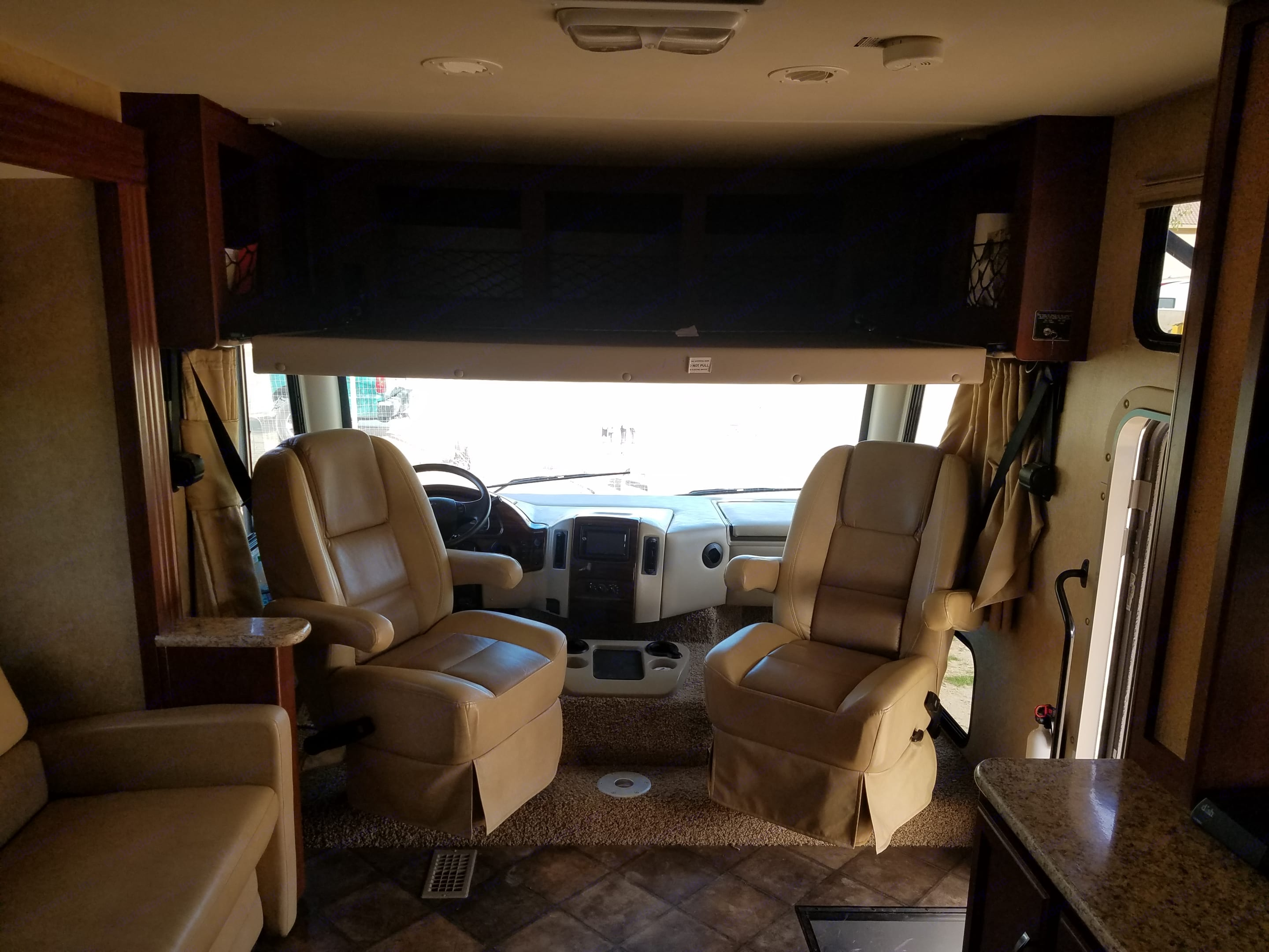Drive and passenger seats swivel for additional common area seating. A full-size bed also folds down above the seats.. Thor Motor Coach A.C.E 2014