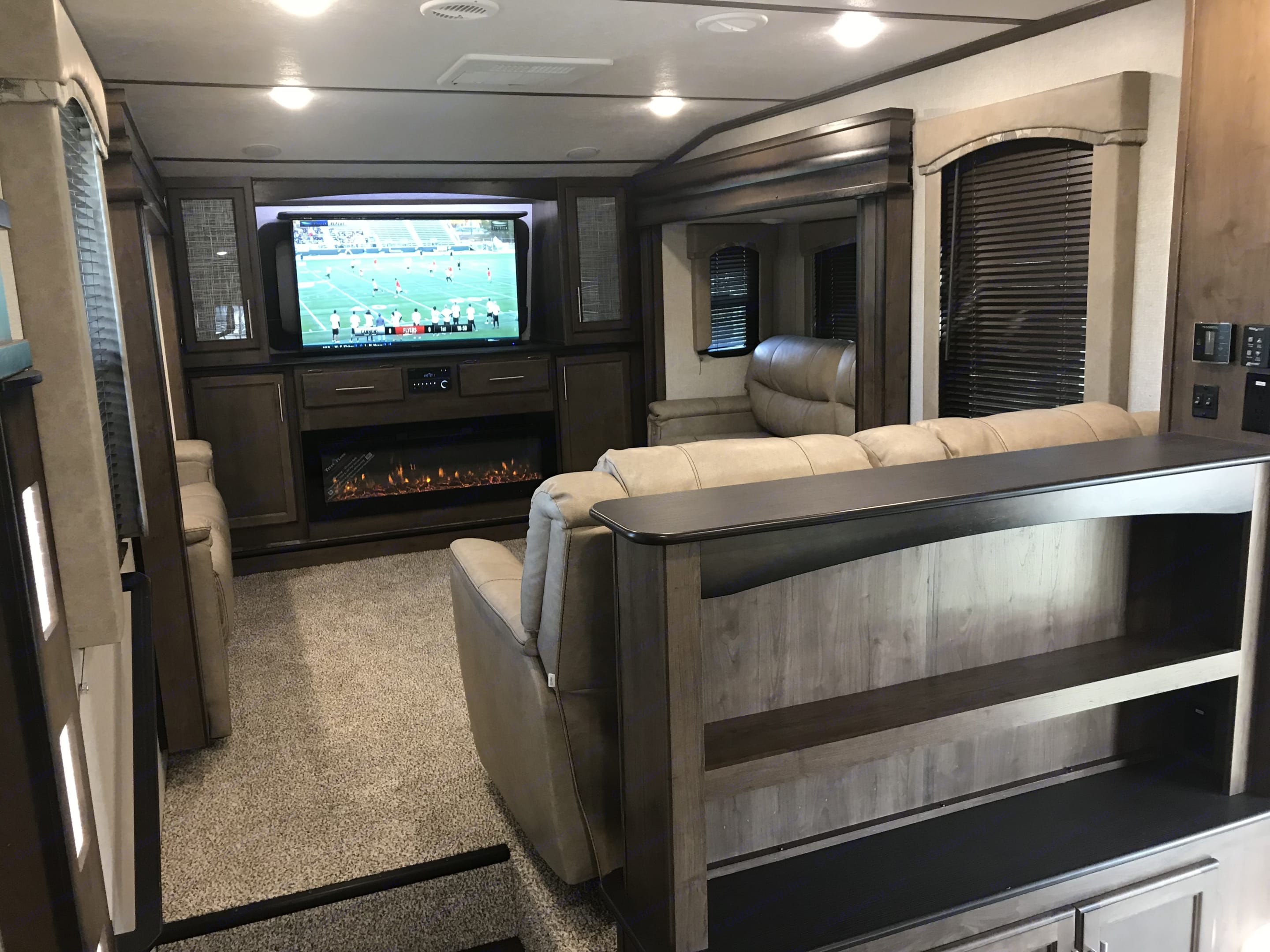 """Front living room with 2 recliners & 2 sofa beds 55"""" pop up tv, am / fm dvd player fire place with remote control. Keystone Cougar 2018"""