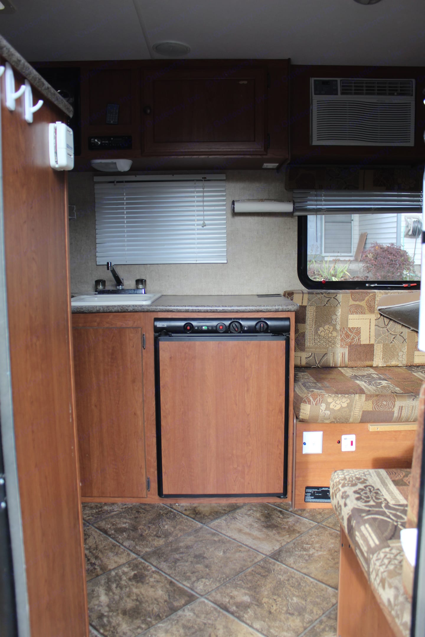 View from the entry door.  Dinette is on the right with A/C unit.  Large fridge with freezer.  Sink and stove are on the left.  Bunk beds and bathroom with shower is also on the left.. K-Z Manufacturing Sportsman Classic 2014