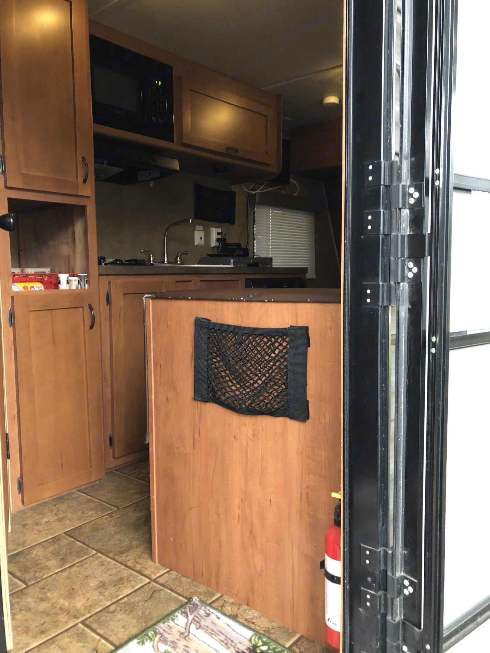 Entry way into the camper has a pouch for easy storage, a fire extinguisher easy to grab and an open view into the camper area. There is storage on the left side of the door way, as well.. Forest River Wolf Pup 2014