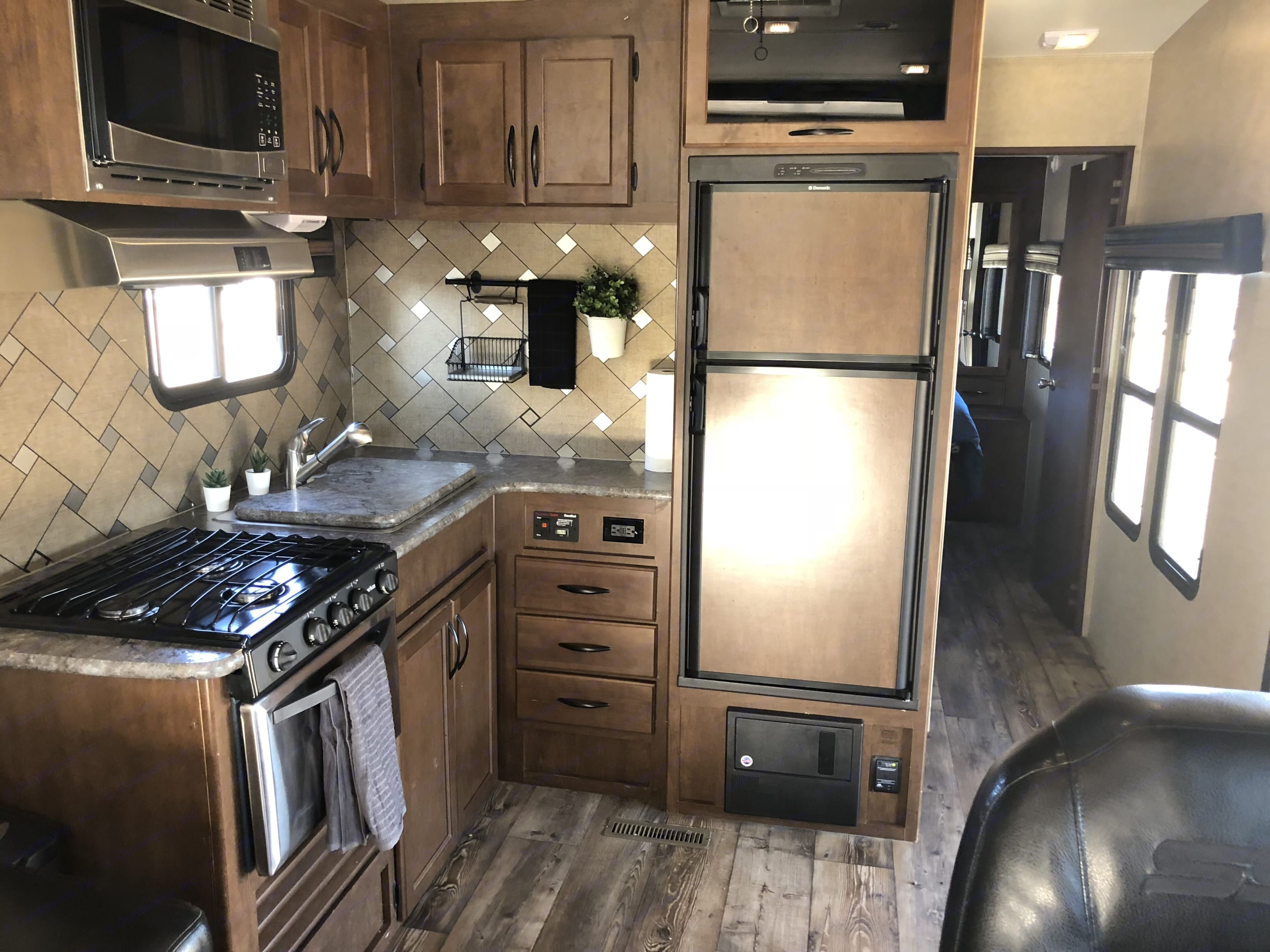 The kitchen includes a refrigerator/freezer, ample counter space and cabinets, a double sink, a three burner range with oven and an overhead microwave.. Pacific Coachworks Sandsport 2016