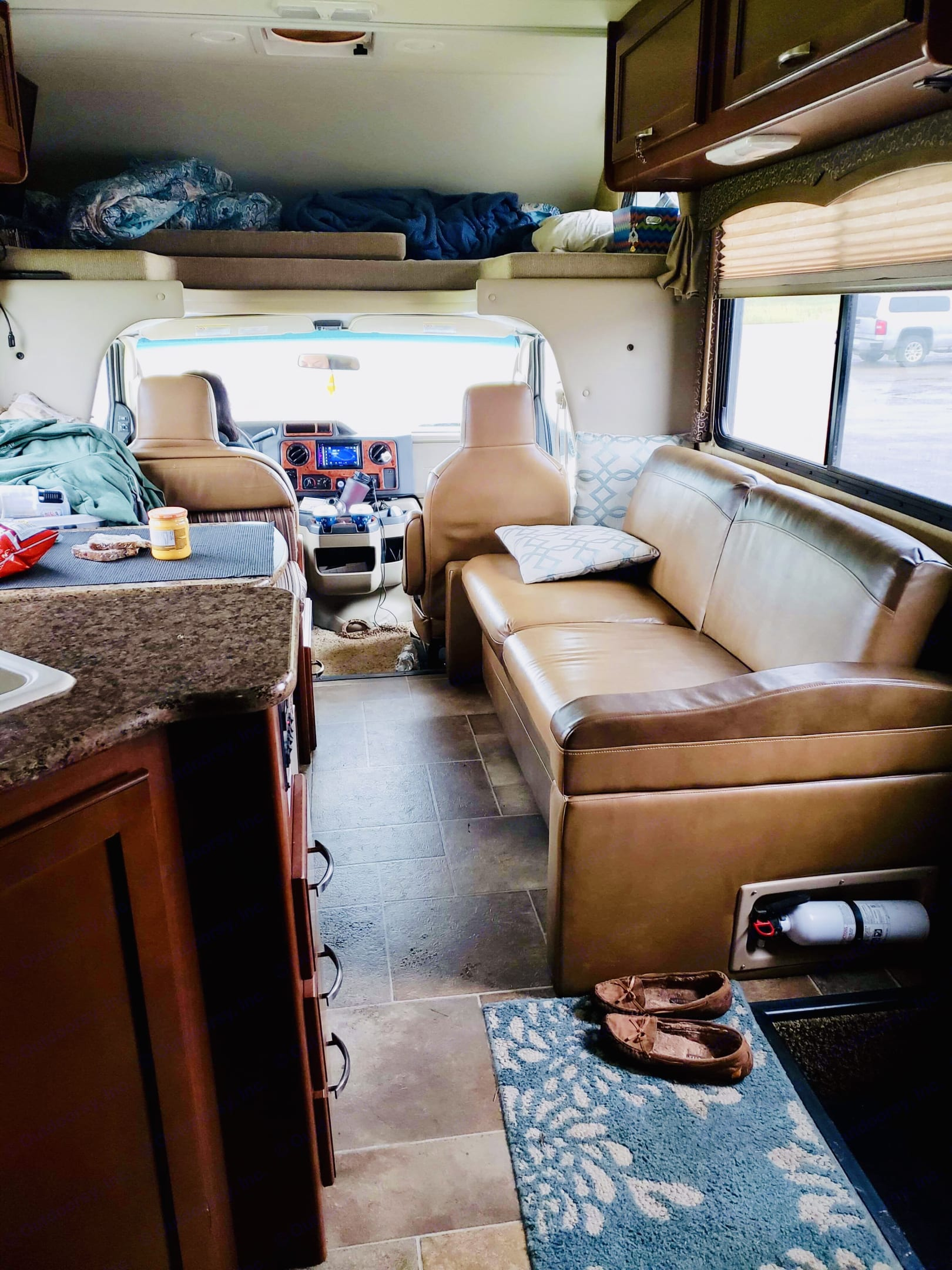 Living area with couch/bed and table/bed. Thor Motor Coach Four Winds 2015