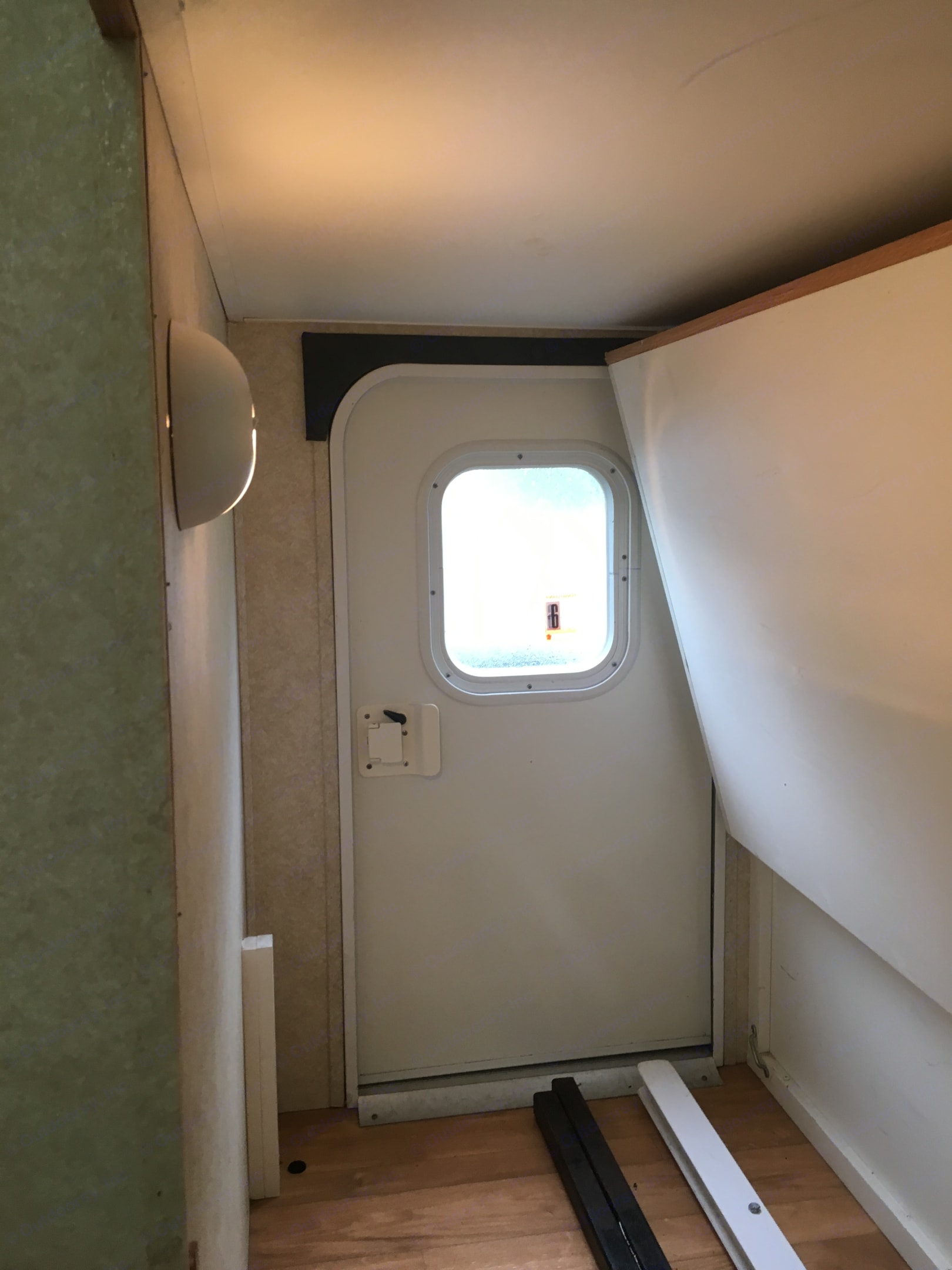 """Interior view showing """"bicycle door,"""" which allows access to lower bunk and storage area.. Keystone Outback 2004"""