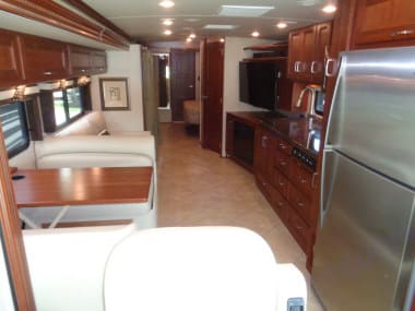 Large living area. Passenger side slide runs the length of the living area and into the master bedroom. . Winnebago Forza 2014