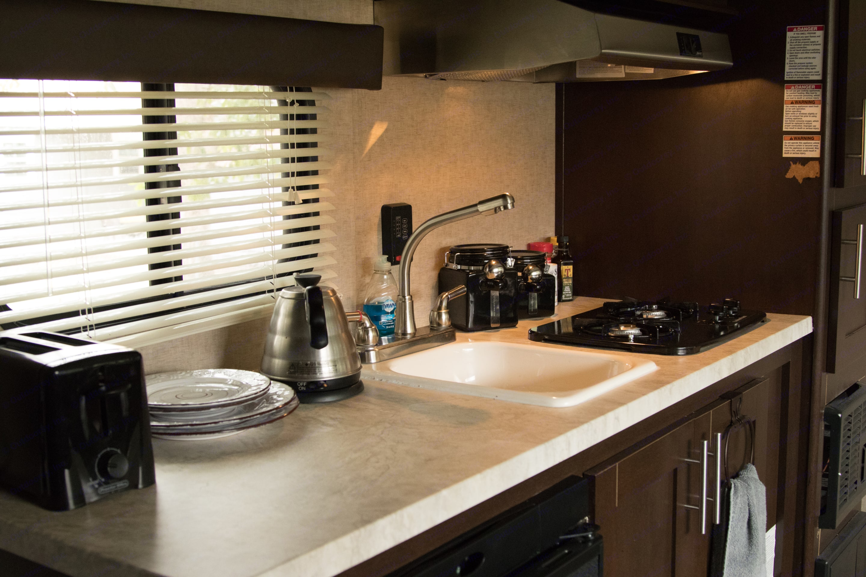 The kitchen includes a two range stove with vented hook, sink with tall faucet, and refrigerator that can run on electricity or propane.. Forest River Cherokee Wolf Pup 2017