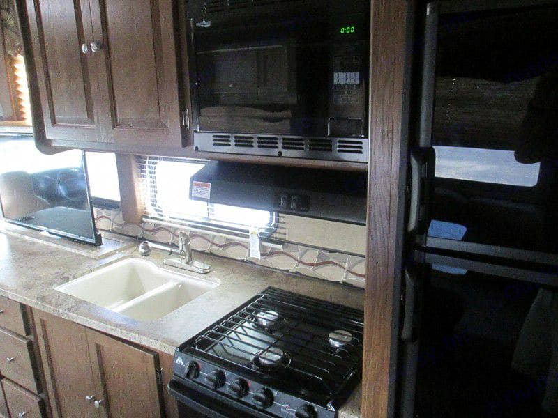 Cooking Area with Microwave, stove and oven.. Coachmen Leprechaun 2016