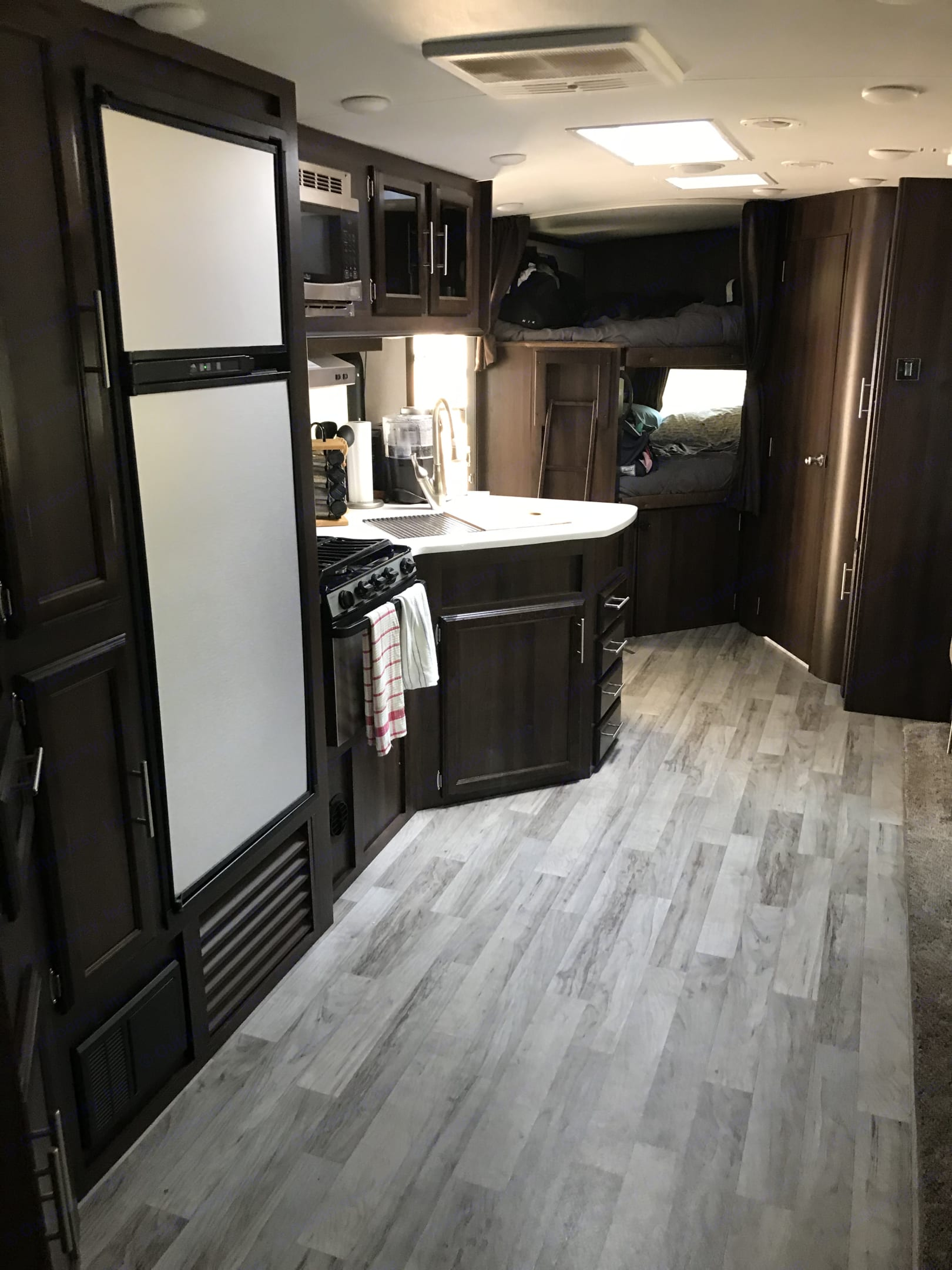 Stainless steel appliances with oversized fridge and solid surface countertops.. Jayco White Hawk 2018