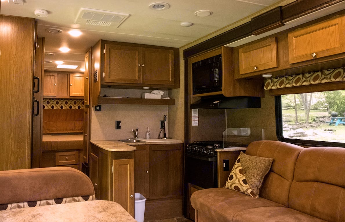 Great interior layout with jacknife couch across from the dinette. The kitchen area can be seen as well with stove, oven, microwave, sink, refrigerator & freezer, and plenty of cupboard space.  All kitchen amenities included!. Coachmen Leprechaun 2017