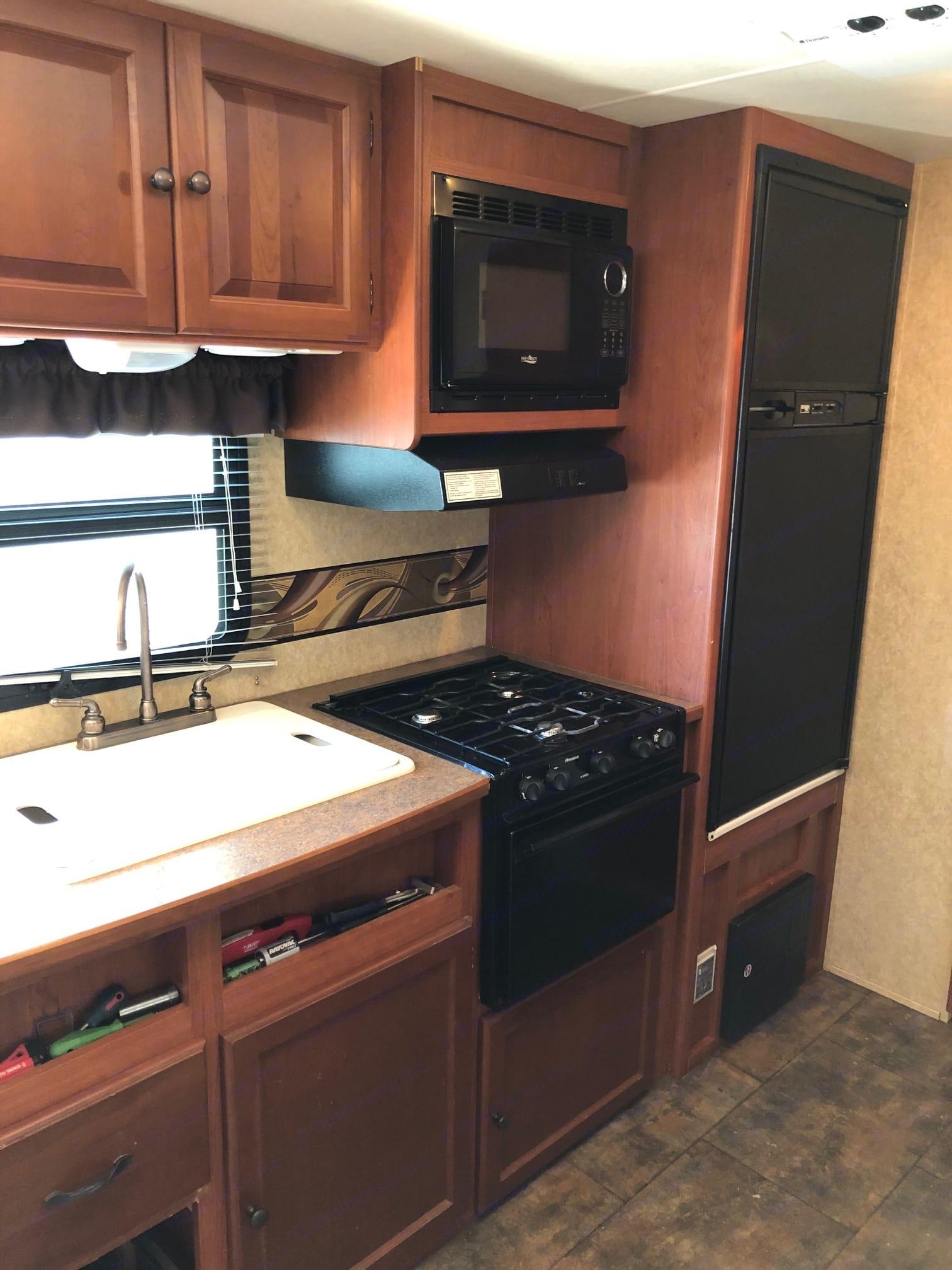 Kitchen with double sinks, propane range and oven, large capacity fridge and freezer. Aerolite Travel Trailer 2012