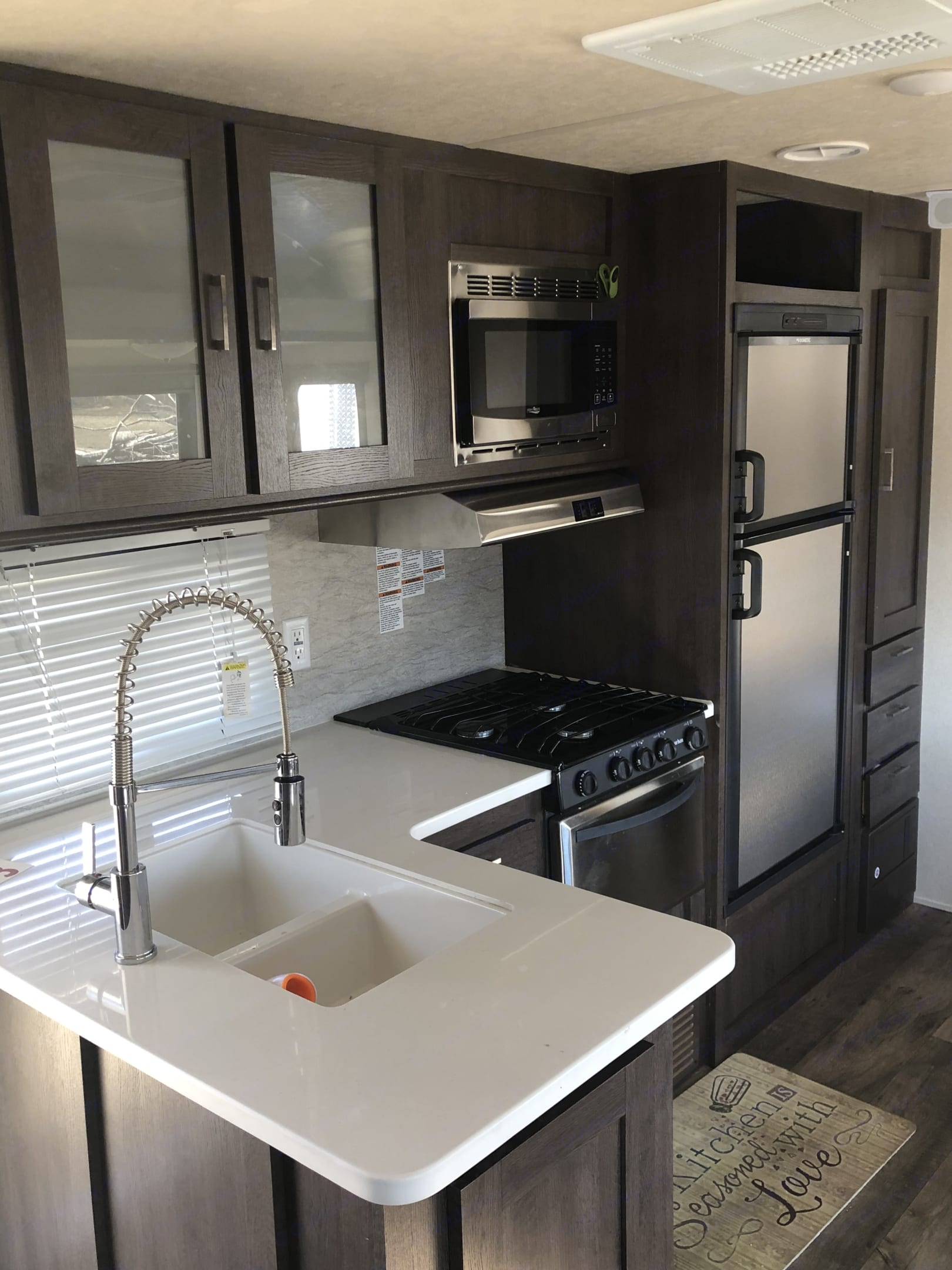 Kitchen with 3 range stove, sink, refrigerator and mircowave . Forest River Wildwood 2018