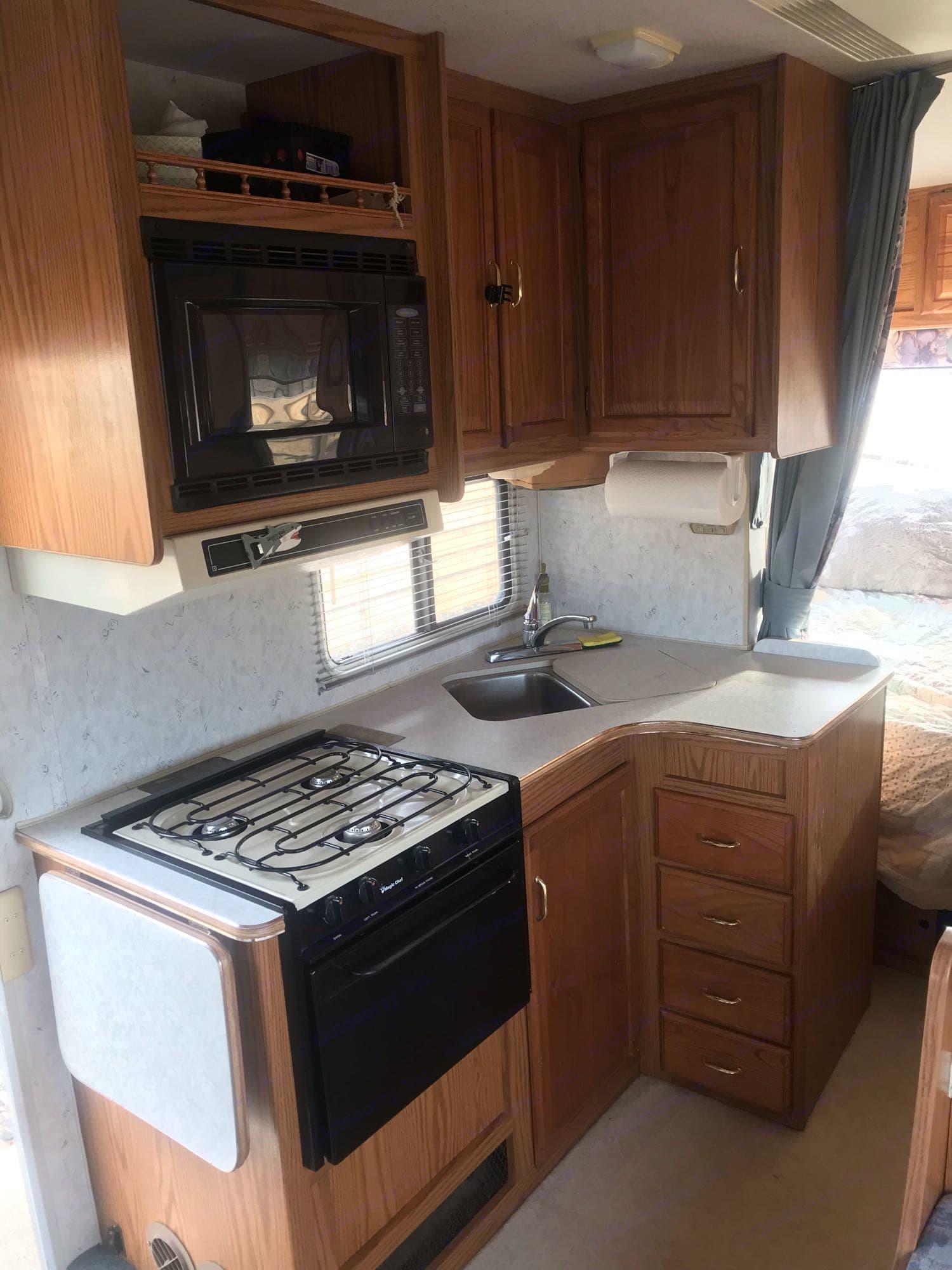 Kitchen with microwave, stove top, sink, fridge, and freezer.. Winnebago Minnie Winnie 1999