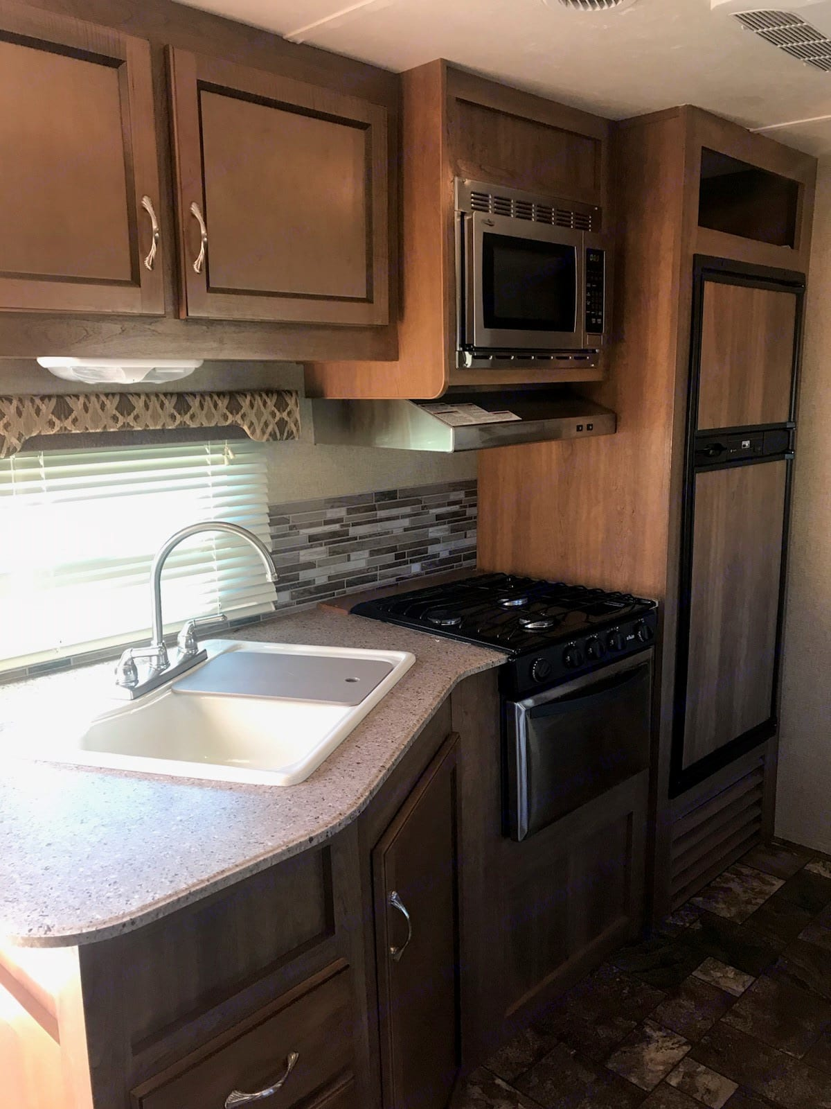 Kitchen area with stove/oven and fridge/freezer combo.. Forest River Catalina 2016