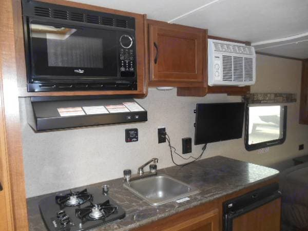 Kitchen includes two burner stove, microwave, range hood, sink, television, and air conditioning unit. . Jayco Jay Flight SLX 2016