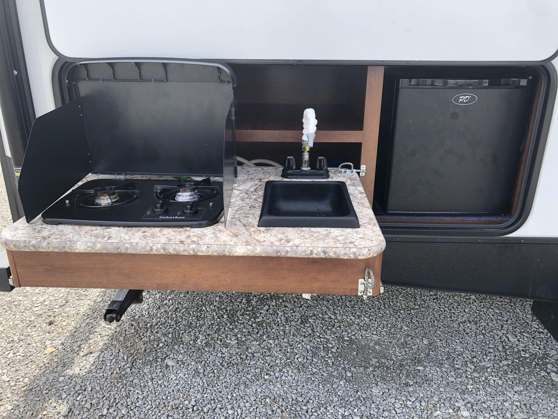 Outdoor kitchen with mini-fridge, two burner propane stove, and sink.. Keystone Passport 2018