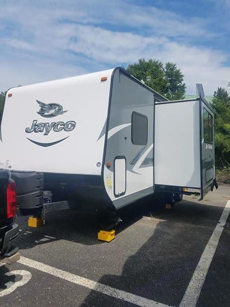This side view shows the extended slide and side storage compartment. The outdoor shower is also located on this side.. Jayco Jay Feather 2016