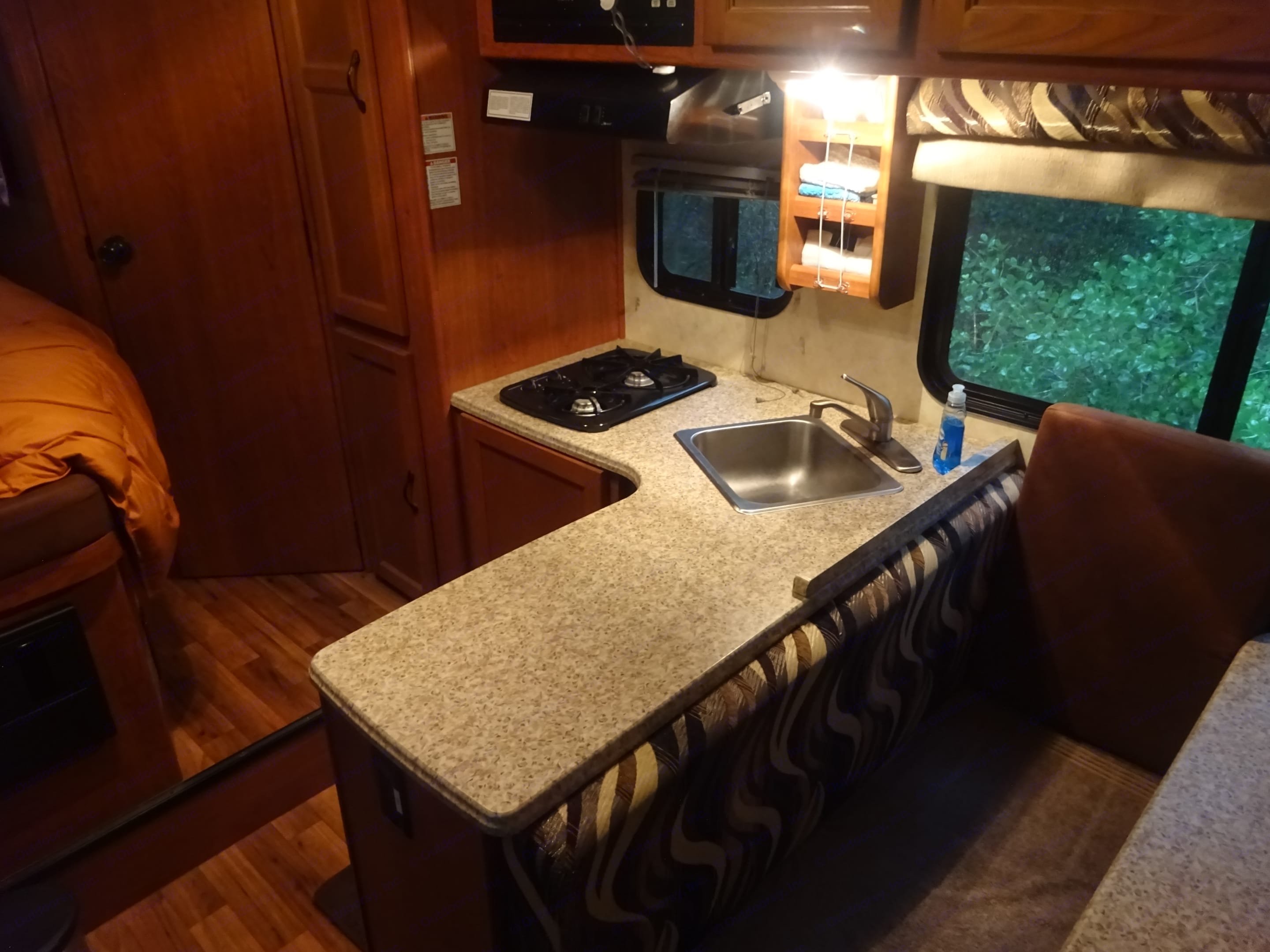 Microwave above stove, Refrigerator at left.  Dining table and bench seat at right.. Coachmen Freelander 2013