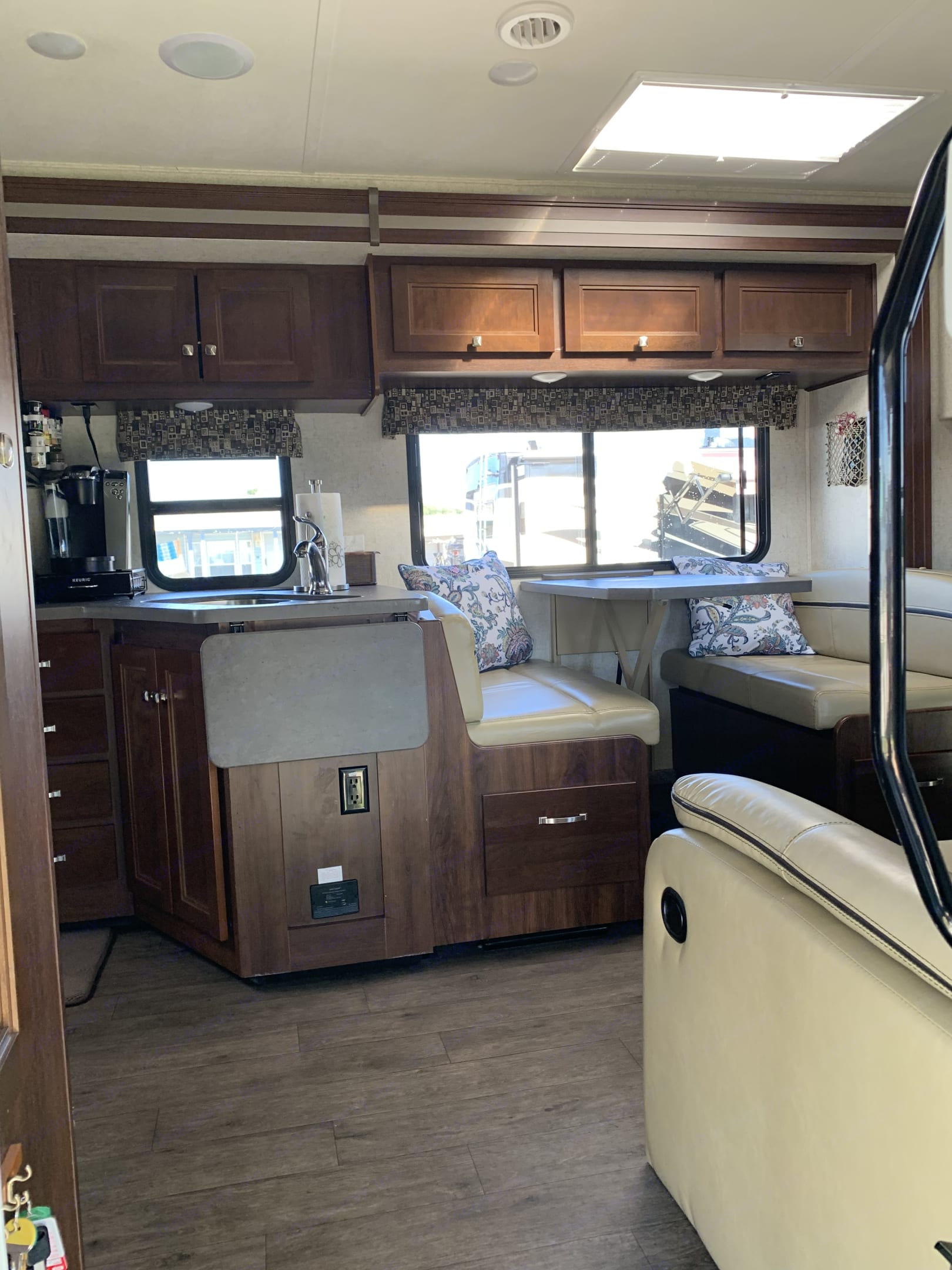 """Kitchen with flip-up countertop extension next to 42"""" x 68"""" dream dinette that converts into bed. . Forest River Sunseeker 2018"""
