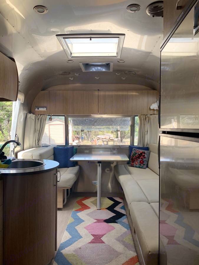 Dining area w. sink and gas stove & microwave. dining table & couch convert to sleep about 3-4 people . Airstream Flying Cloud 2018