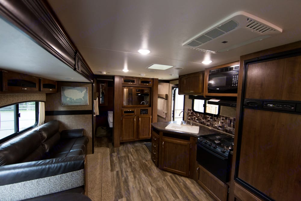 Large kitchen features a nice large fridge and freezer, a large pantry cupboard, microwave, stove top and oven, and a large sink. Jayco Jay Feather 2017