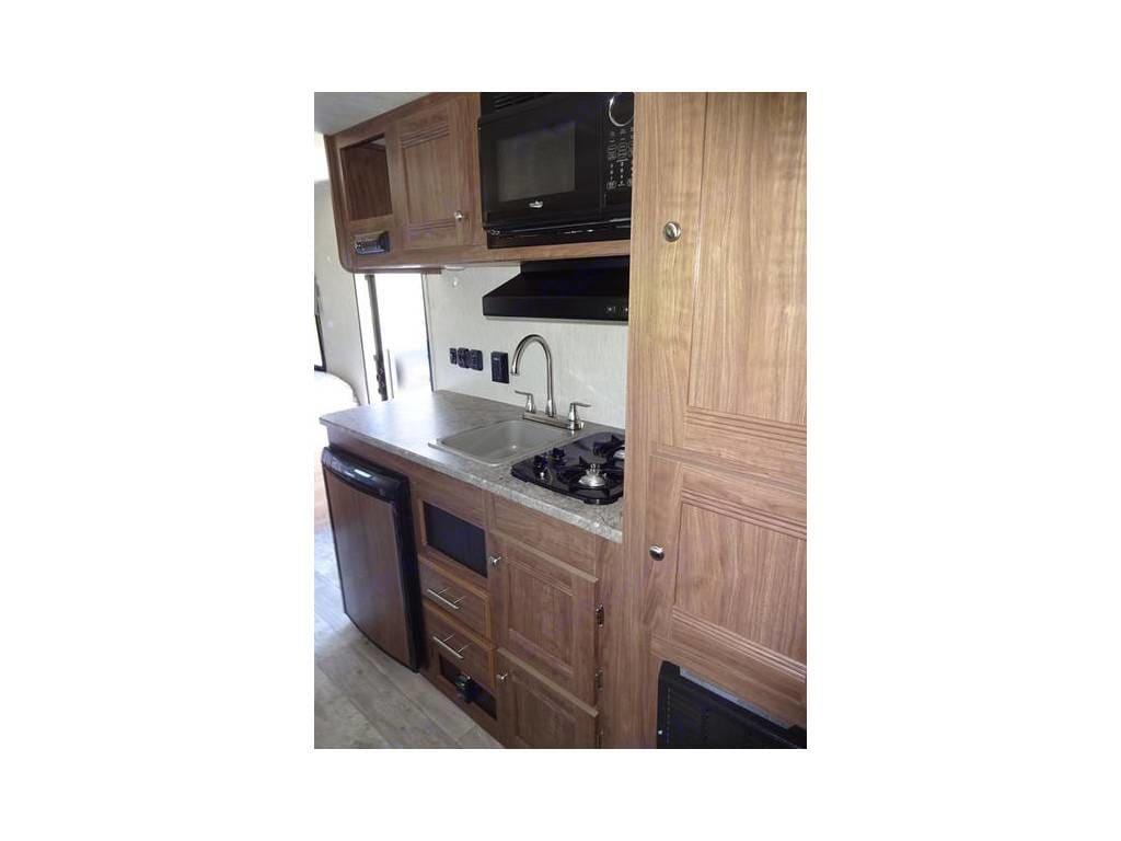 Kitchen includes sink, fridge, 2-burner stove, and microwave.. Heartland Pioneer 2018