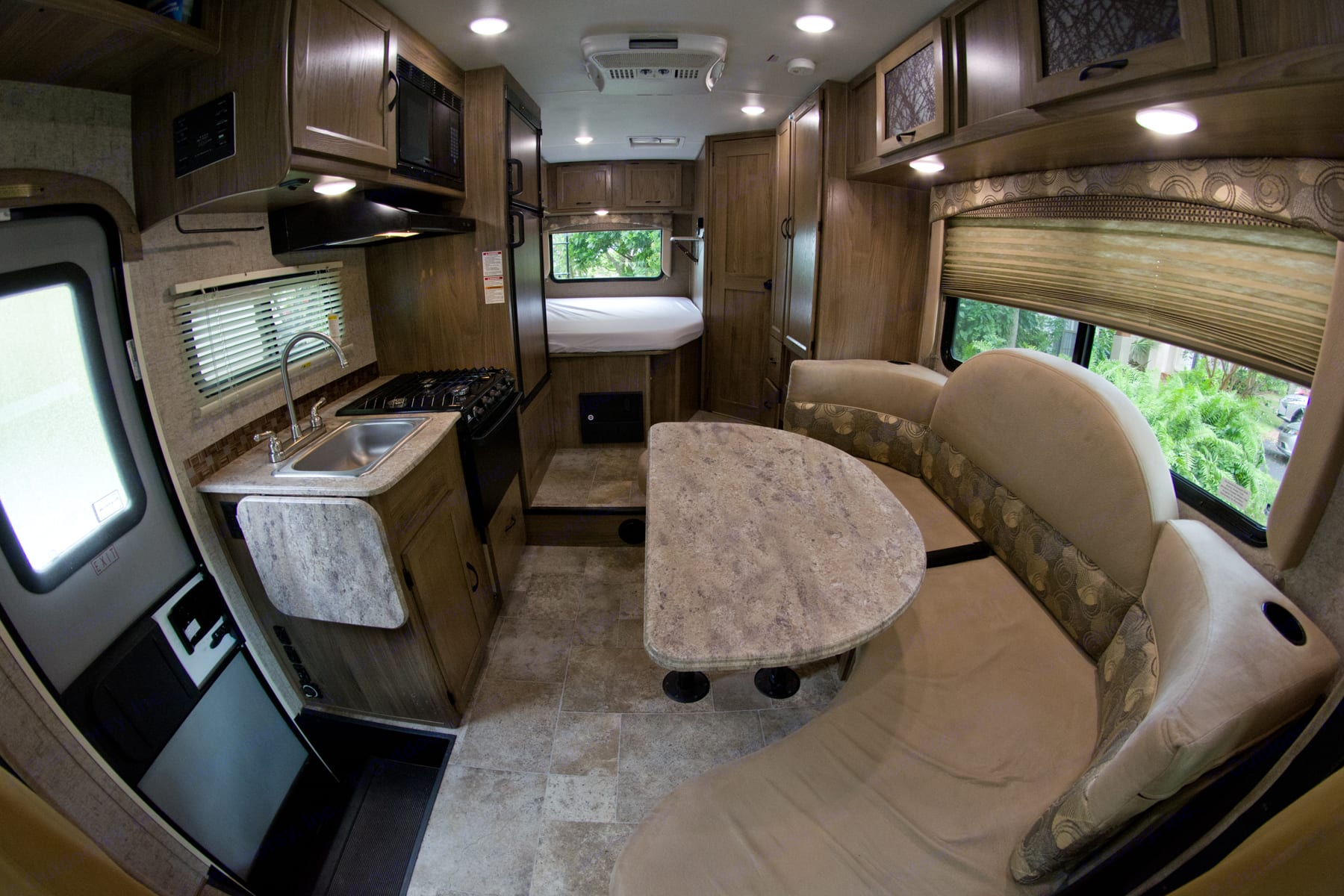 Dinette, Kitchen entry to the Class C Camper. In the far end bed near walk in shower, bathroom sink and toilet. The wall to the left has another flat screen DVD TV Player.. Coachmen Freelander 2017