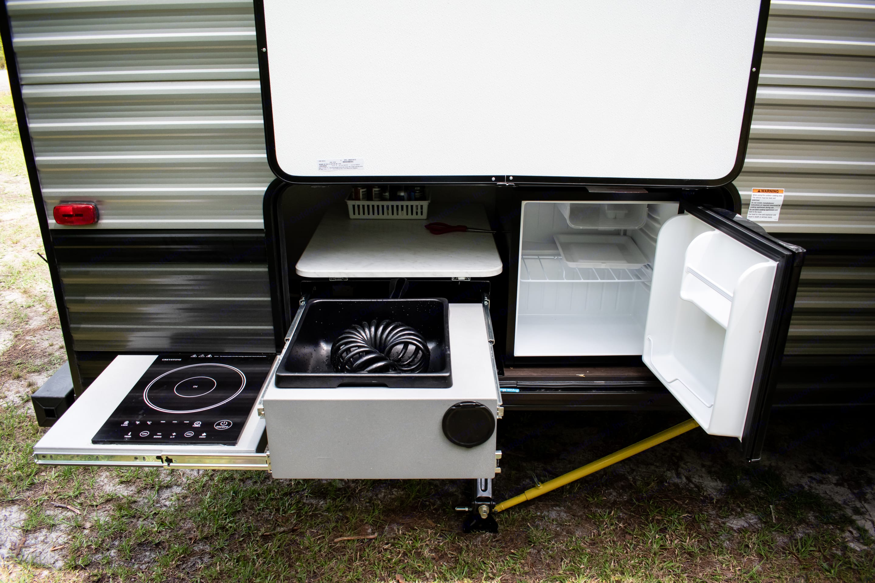 Outdoor kitchen with convection stove, mini fridge, and wash bin. Out door shower is cold water only and part of the outdoor kitchen. . Forest River Cruise Lite 2020