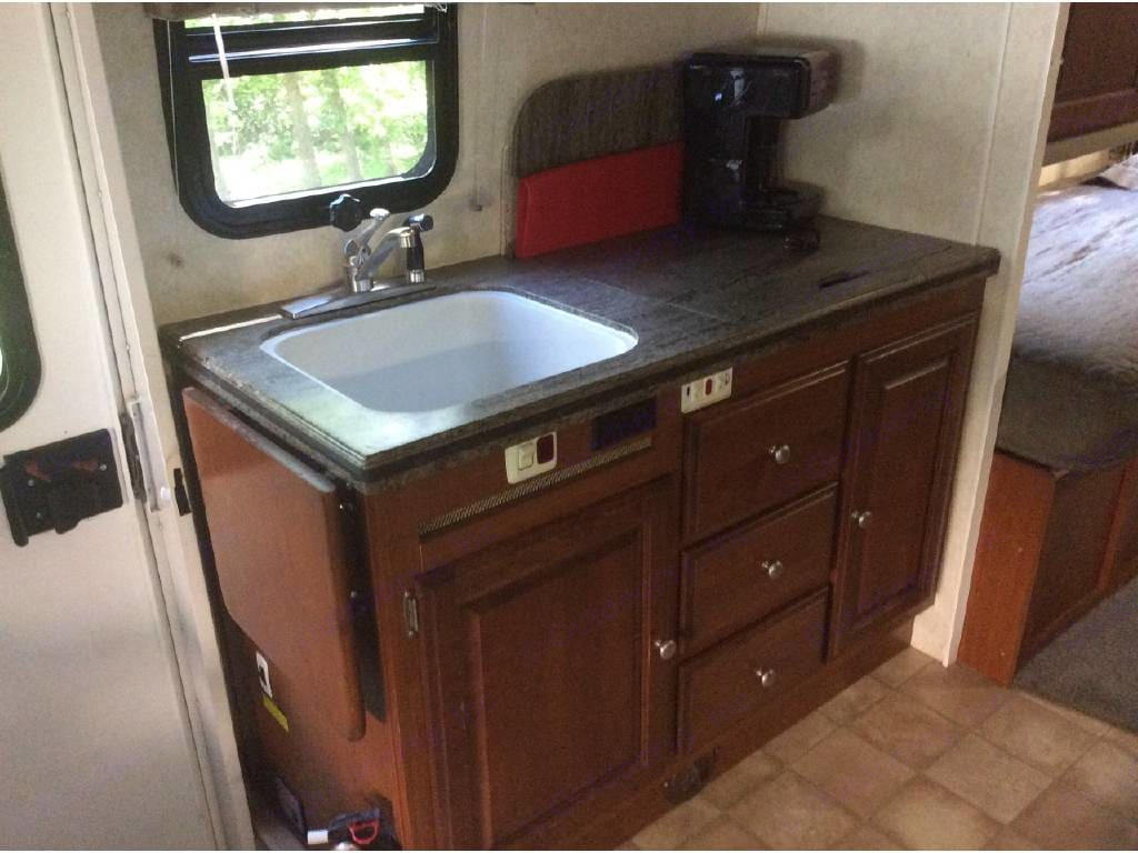 Sink, stove, coffee maker, microwave/convection oven above. Silverware for four, microwave dishes, and towels are provided. Just bring your food and pillow to enjoy you outdoor adventure. . Phoenix USA Cruiser 2552 2011