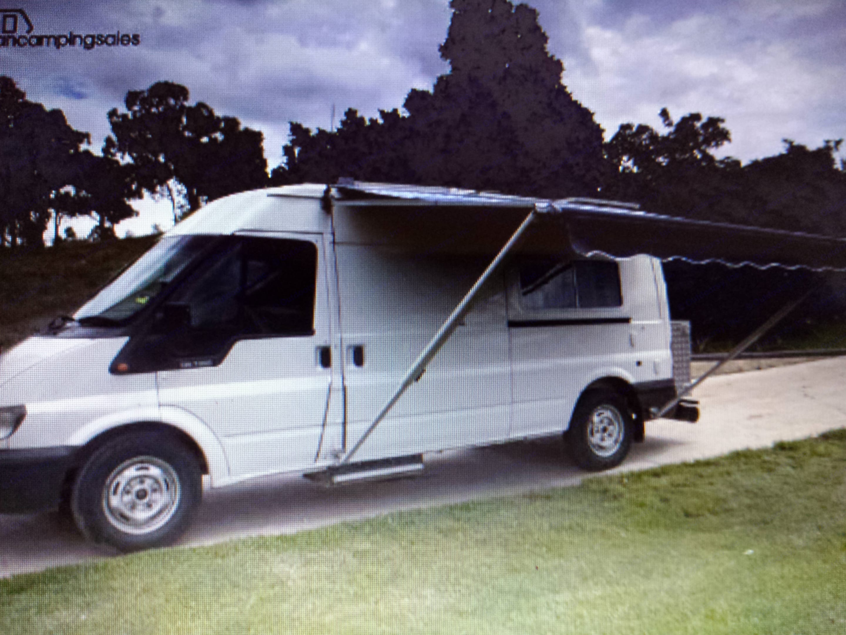Side awning extended. Can see the electric step for sliding door.. Ford Transit Custom 2006