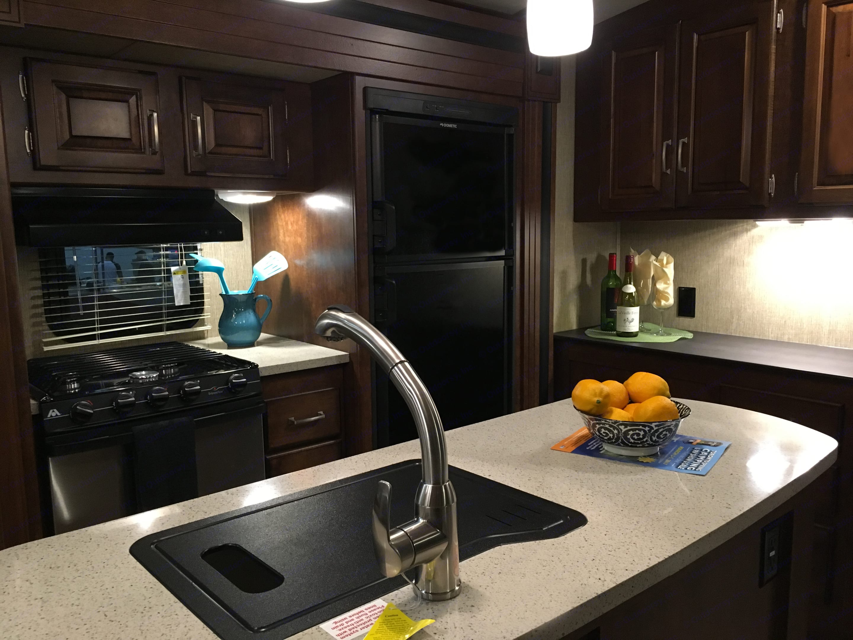 Spacious, fully functional kitchen featuring a corian countertop island with a large, deep sink. Three burner gas stove and oven,  food pantry, 8 cu.ft. fridge with freezer that runs on electric or propane.. Keystone Outback 2017