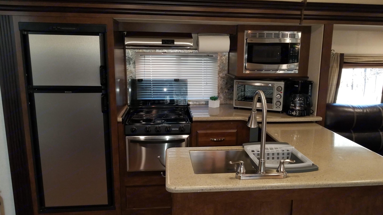 Kitchen. Includes: 3 burner stove, toaster oven, sink, coffee pot & filters, refrigerator, assorted pots, baking sheet and broom & dustpan. . Forest River Heritage Glen 2017