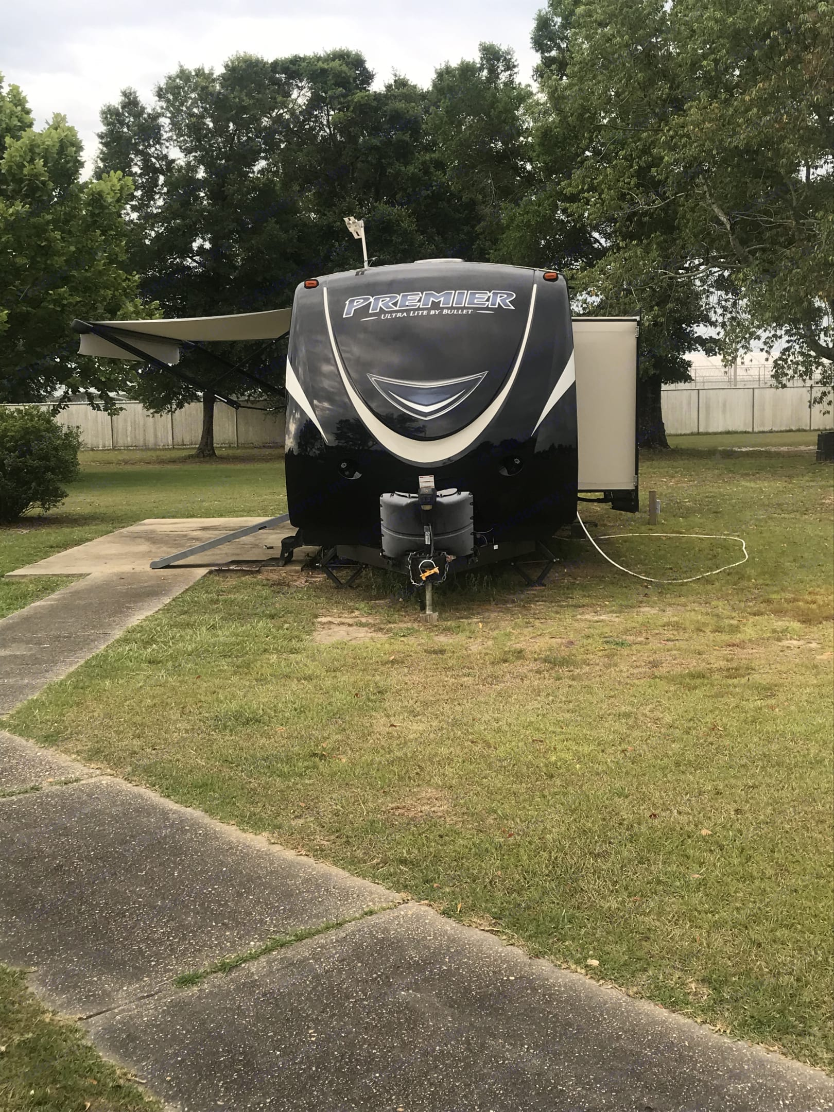 Front view of trailer: Awning extended, propane, electric jack and first slide. Keystone Bullet Premier 2016